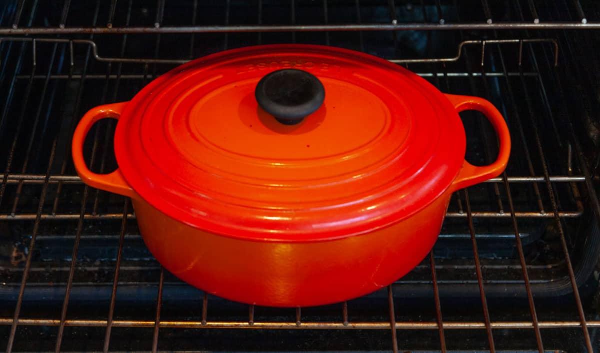 an orange Le Creuset Dutch oven inside of an oven