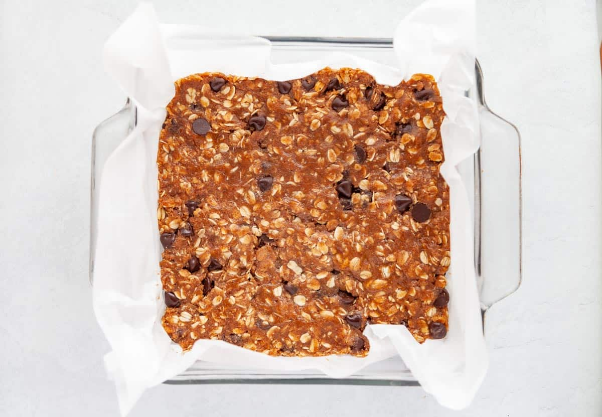 batter for oat and chocolate bars pressed into a pan lined with parchment