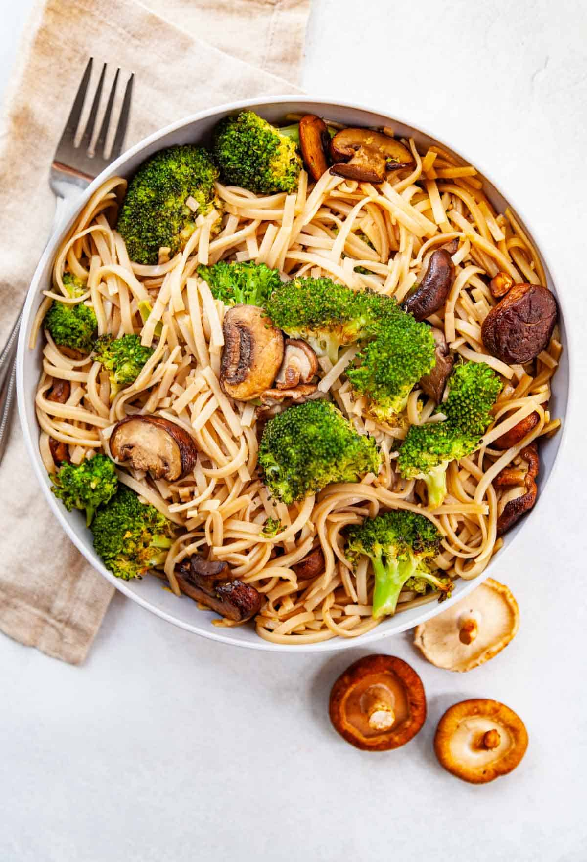 bowl of stir-fried brown rice noodles with roasted broccoli and mushrooms
