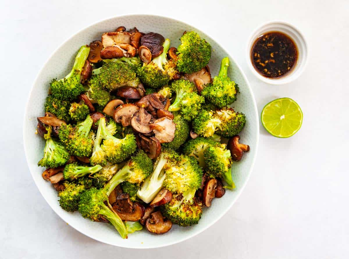 bowl of roasted broccoli and mushrooms with stir-fry sauce on the side