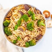 bowl of brown rice noodles with broccoli and mushrooms