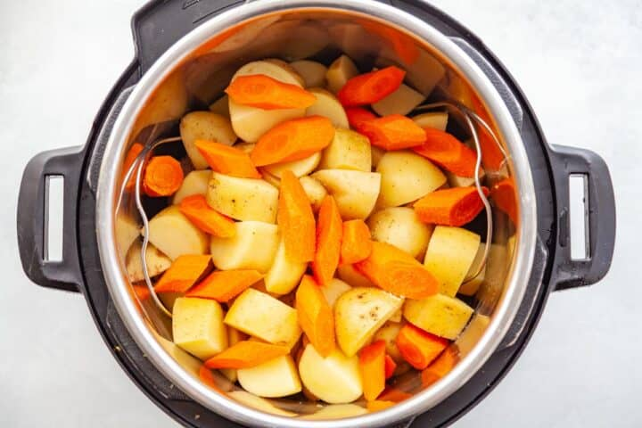 raw potatoes and carrots in a pressure cooker
