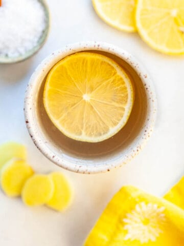 a mug of savory broth with a lemon slice